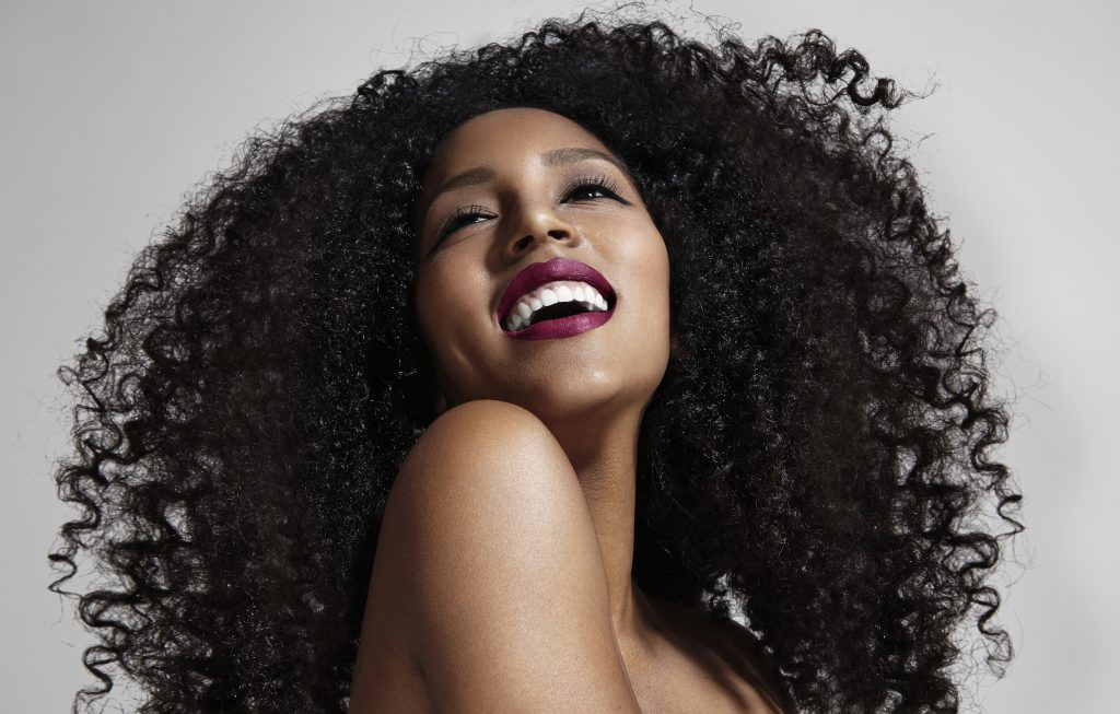laughing woman with afro hair yensi style